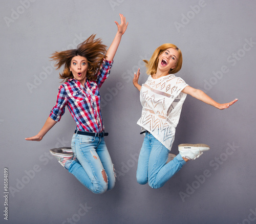 Girls jumping over gray background