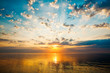 Beautiful sunrise with clouds, lightstreaks and golden water.