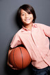 attractive little boy smiling while holding basketball