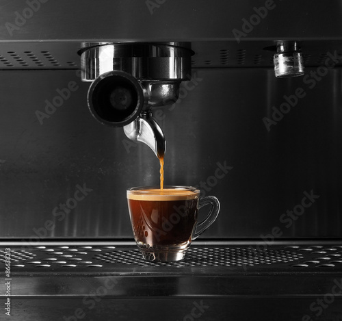 фотография Hot coffee flow to a cup on espresso machine