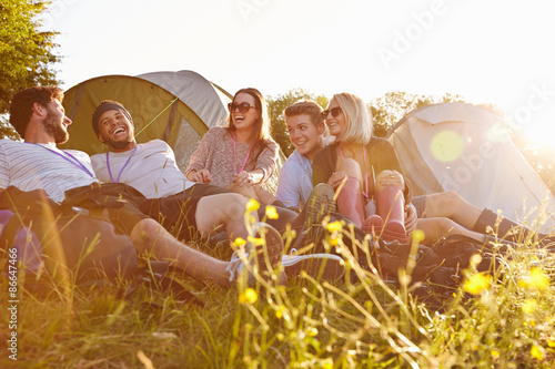 In de dag Kamperen Group Of Friends Relaxing Outside Tents On Camping Holiday