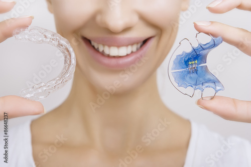 Fotografia  Smiling girl Holding Retainer for Teeth and Tooth Tray