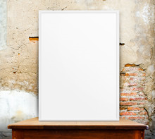 Empty White Frame On Wooden Table At Grunge Concrete Wall In Bac
