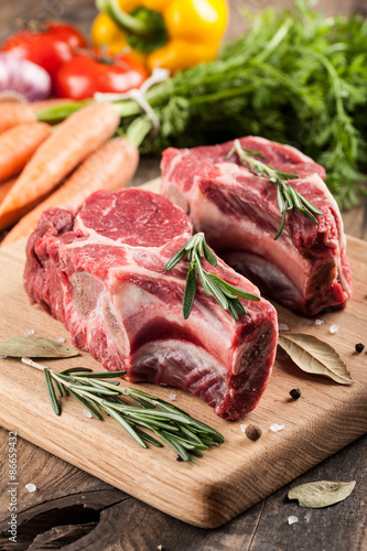 Staande foto Vlees Raw beef meat on cutting board and fresh vegetables