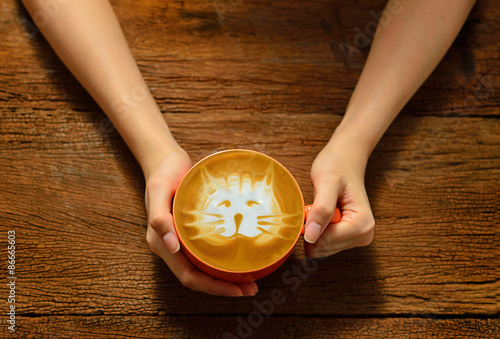 Wall Murals Cafe Woman holding cup of coffee latte on wooden table