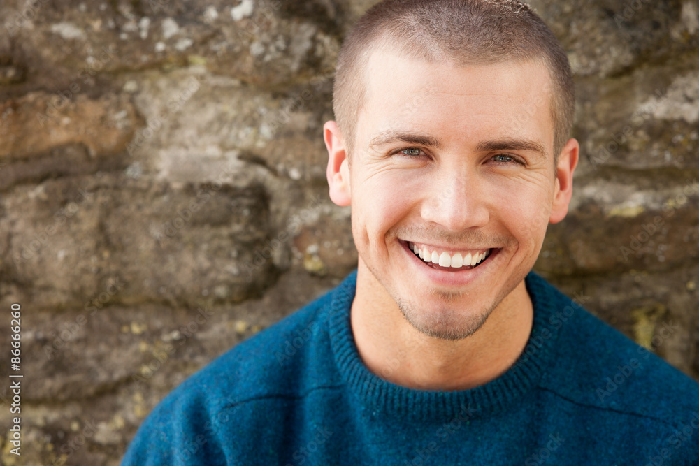 Fototapety, obrazy: Attractive young man sitting outside. He is smiling at the camera.