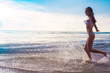 carefree woman running in the sunset on the beach. vacation
