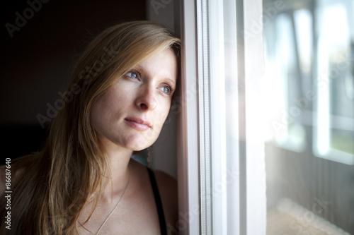 Mujer rubia mirando pensativa por la ventana Tapéta, Fotótapéta