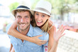Cheerful man giving piggyback ride to girlfriend