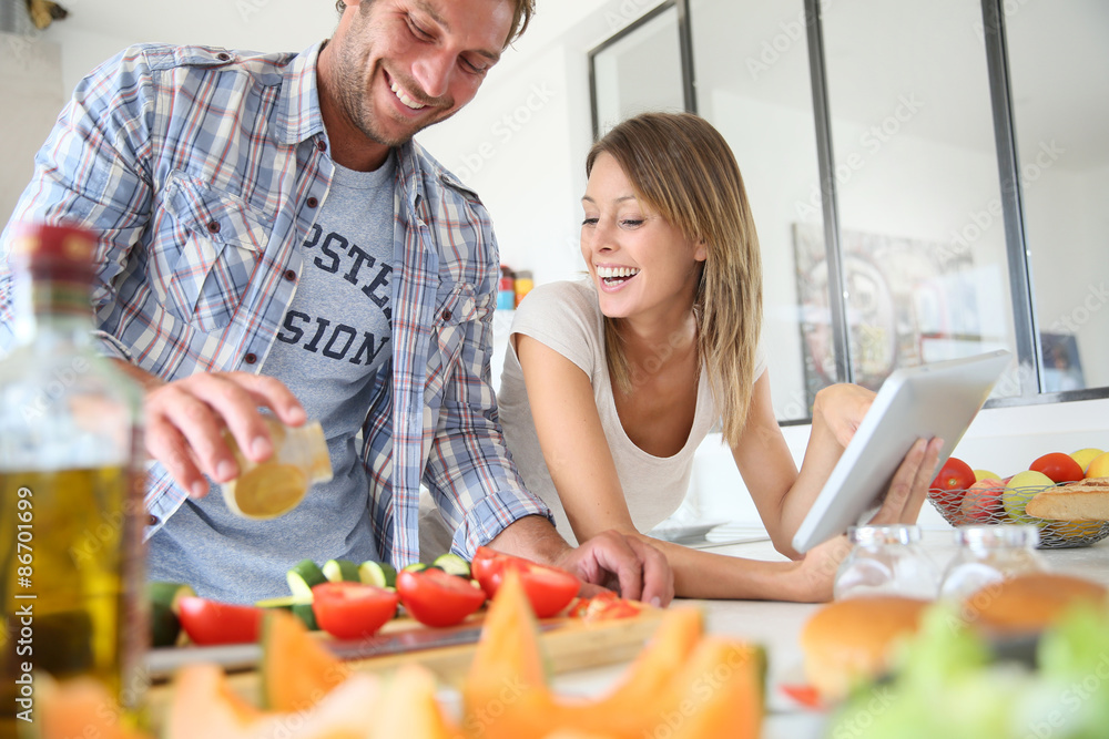 Fotografie, Obraz  Cheerful couple in kitchen cooking dinner, using tablet