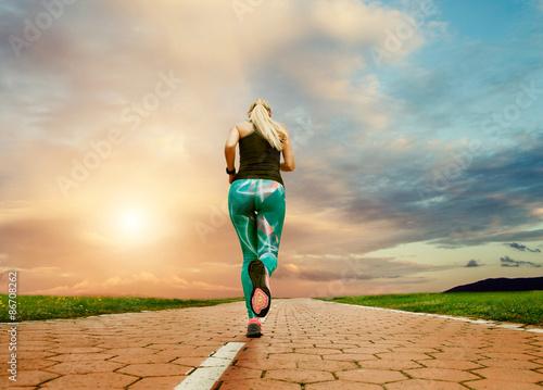 Fototapeta Young blonde girl evening jogging with great cloudscape obraz na płótnie
