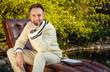 Young handsome man sit in luxury sofa in summer garden.