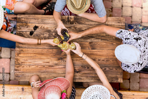 Hand of people cheers with alcohol cocktails at natural handcrafted wooden desk Poster