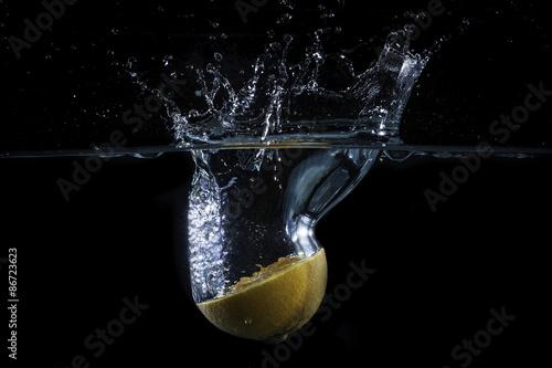 Valokuvatapetti Mezzo arancio cade nell'acqua generando schizzi e gocce
