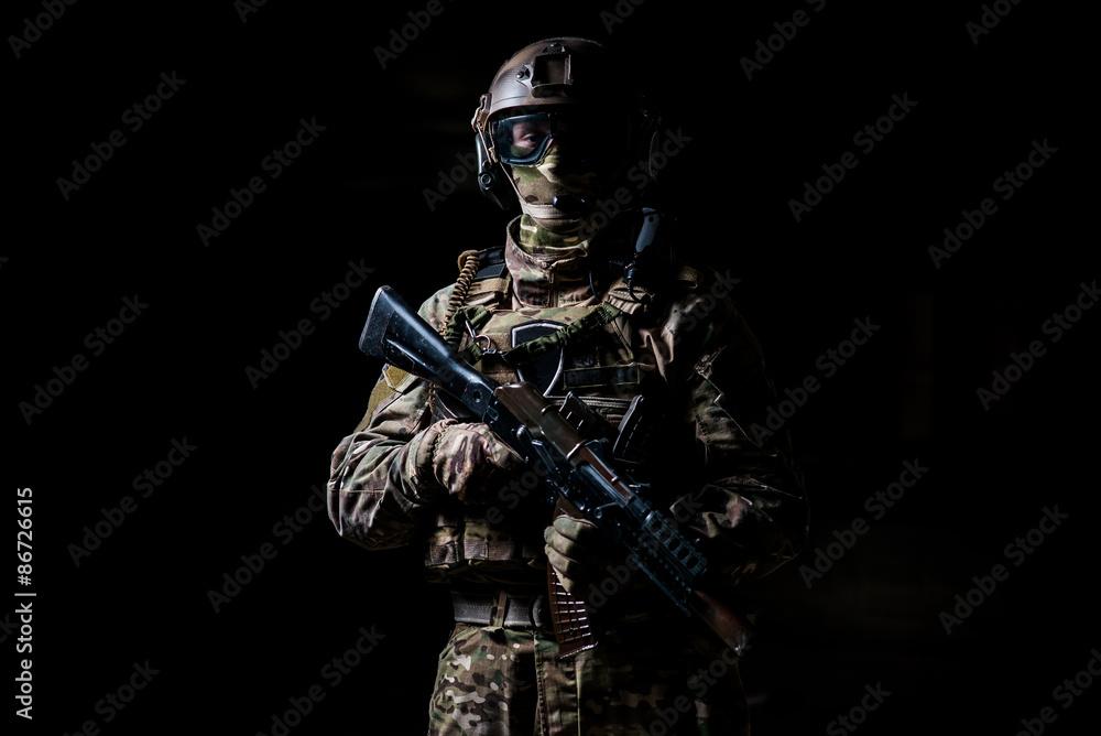 Fototapeta Soldier in camouflage hold machine gun