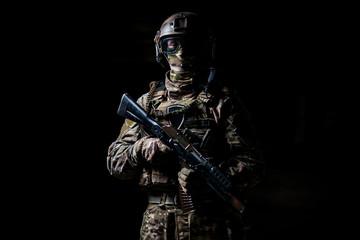 Soldier in camouflage hold machine gun