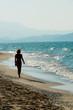 Woman strolling on sandy beach of Crete shore, Greece