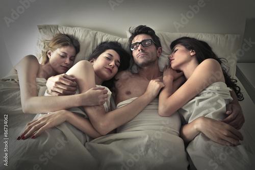 Photo  Man sleeping with three women