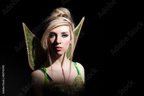 Fototapeta Young blonde woman dressed as fairy on dark background