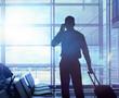 canvas print picture - Geschäftsreisender mit Koffer telefoniert im Flughafen