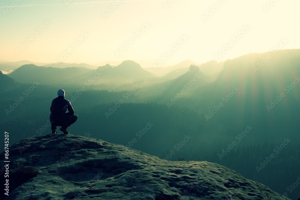 Fototapety, obrazy: Hiker sits on a rocky peak and enjoy the mountains scenery