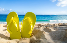 Yellow Flip Flops On The Sandy Beach
