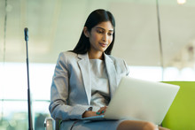 Indian Business Traveler Using Laptop At Airport