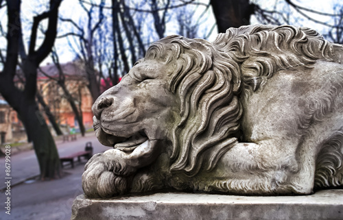 Poster Artistique Powerfull sculpture of stone lion in Lviv