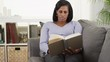 Senior black woman reading book on couch at home
