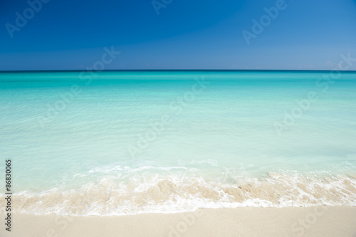Photo Stands Caribbean Shore of classic turquoise Caribbean Sea dream beach under bright blue sky in Varadero, Cuba