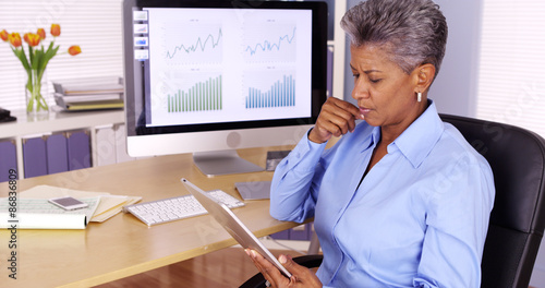 Senior african manager working at desk with tablet