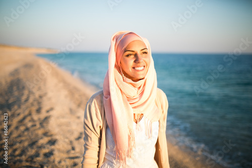 Young beautiful happy muslim woman outdoors portrait.Seaside,beach walk.Beautiful arab saudi woman face posing on the beach with the sea in the background