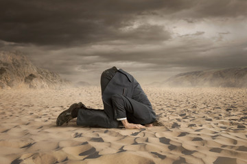 Fototapeta Young businessman hiding head in the sand