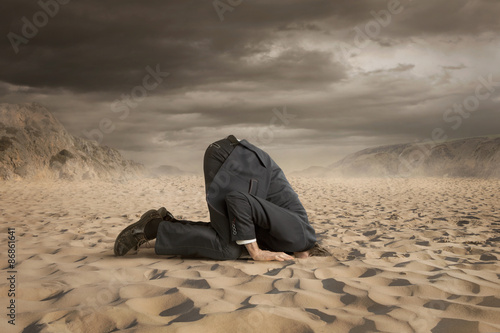 Young businessman hiding head in the sand Принти на полотні