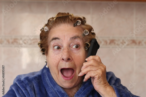 Old lady with curlers surprised on the phone