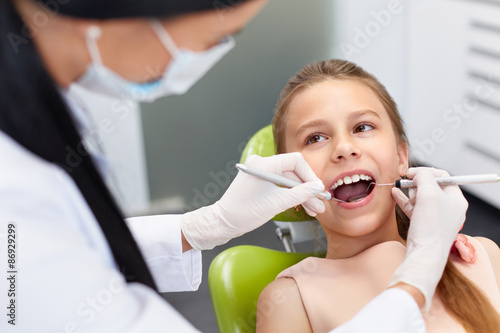 Teeth checkup at dentist's office. Dentist examining girls teeth Plakat