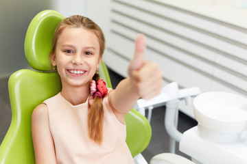 Portrait of happy girl shows thumb up gesture at dental clinic