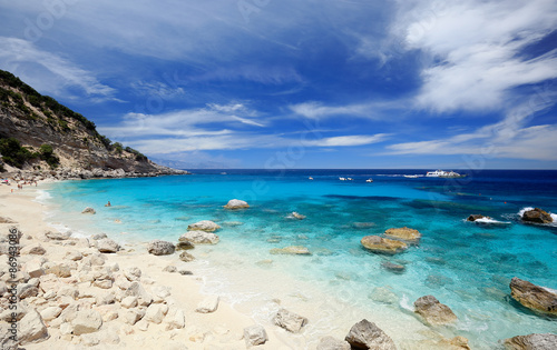 Photo  Cala Mariolu on a clear day with soft white clouds, Sardinia