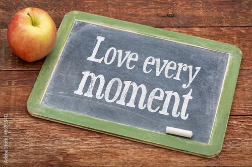 Fotografía  Love every moment advice on blackboard