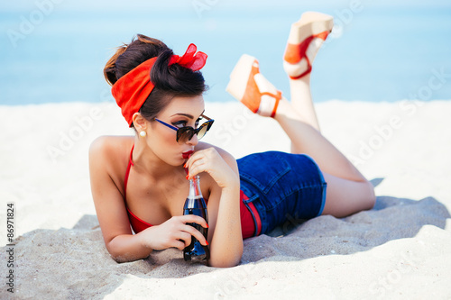 Photo  Pin-up at sea drink and watch over sunglasses