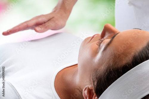 Photo  Woman at reiki session with therapist hand in background.