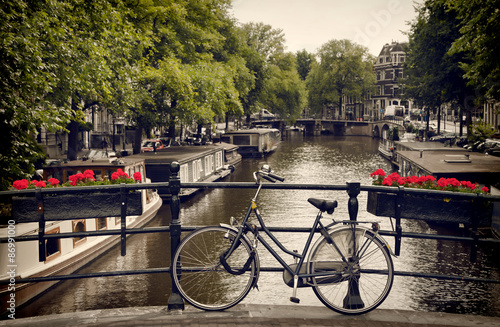 Fotografiet  Bicycle Parked on the Pedestrian Bridge Overlooking a Canal in Amsterdam