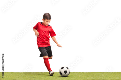 Little kid kicking a football