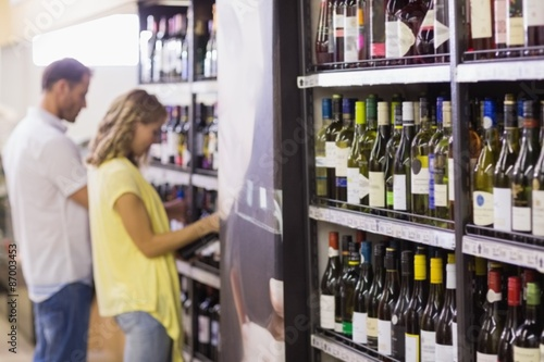 Pretty woman and handsome buying a wine bottle Canvas Print