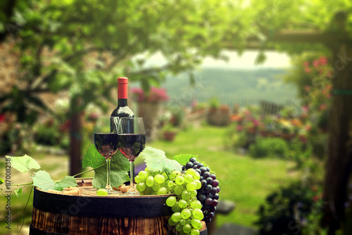 Red wine with barrel on vineyard in green Tuscany, Italy - 87008238