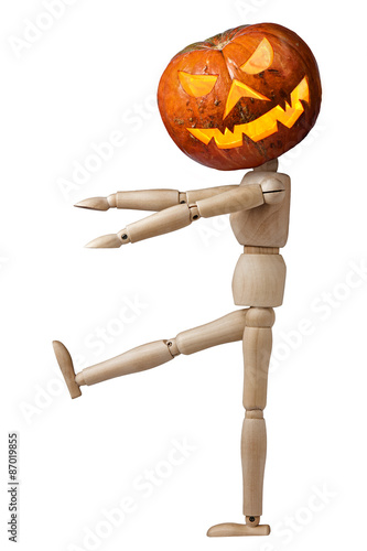 Fotografía  Wooden mannequin with spooky pumpkin walking and scaring isolated