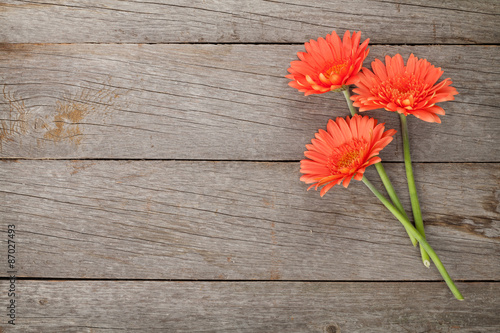 Poster Gerbera Wooden background with orange gerbera flowers