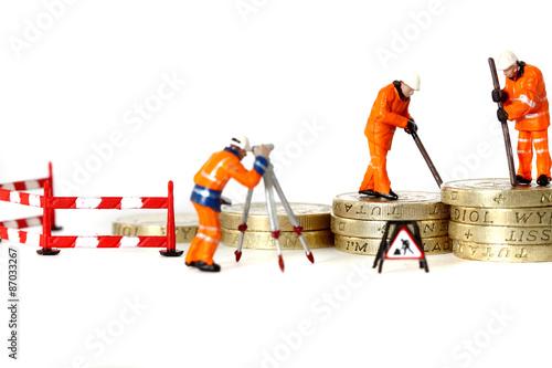 Fotografie, Obraz  Miniature construction workers pound coins