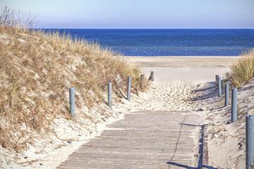 Fototapeta Do hotelu Wooden sandy path to the beach.