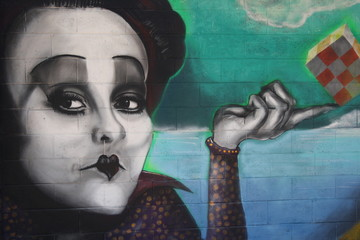 Milan, Italy: street art, a murales of woman with a cube in hand